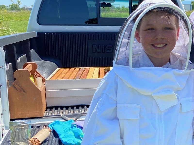 Maddox Shivley collecting honey from his bees.