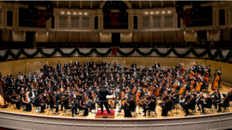 Here is a picture of an adult band and an orchestra playing together in a concert.