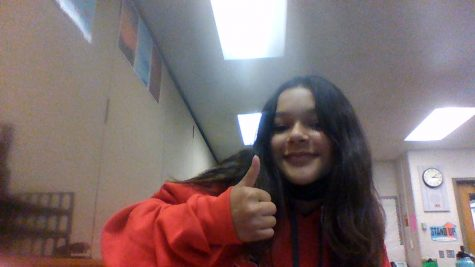 This is a picture of Mariah Vega, she is currently holding a thumbs up.